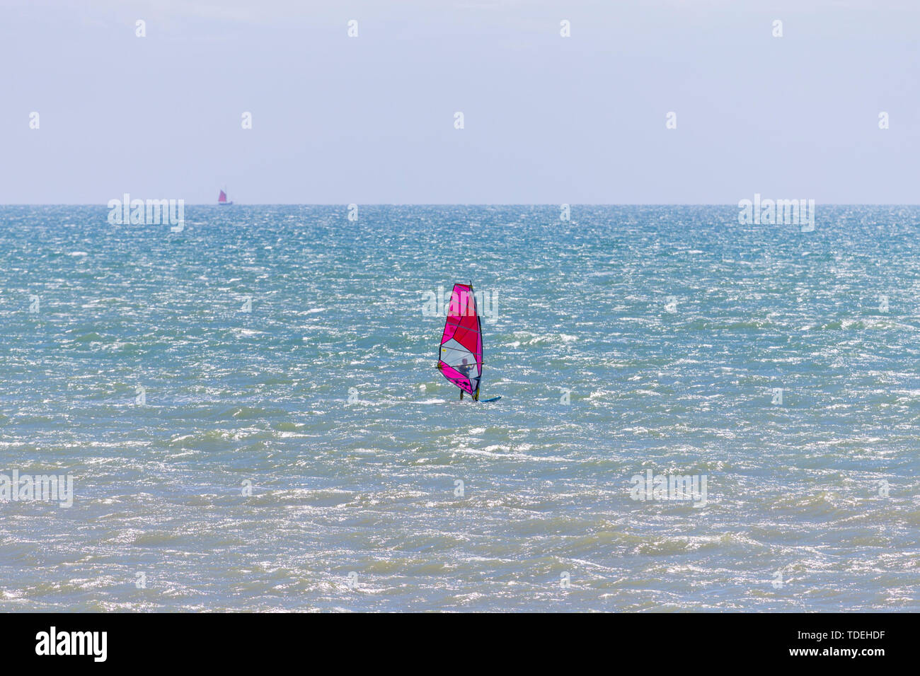 Camber, East Sussex, UK. 15th June, 2019. UK Weather: A beautiful sunny start to the weekend in Camber, East Sussex as people arrive to the Camber Sands beach to enjoy the warm weather. A solitary wind surfer with a bright pink sail takes to the sea on a warm and pleasant day with a slight breeze in the air. Credit: Paul Lawrenson 2019, Photo Credit: Paul Lawrenson/ Alamy Live News Stock Photo