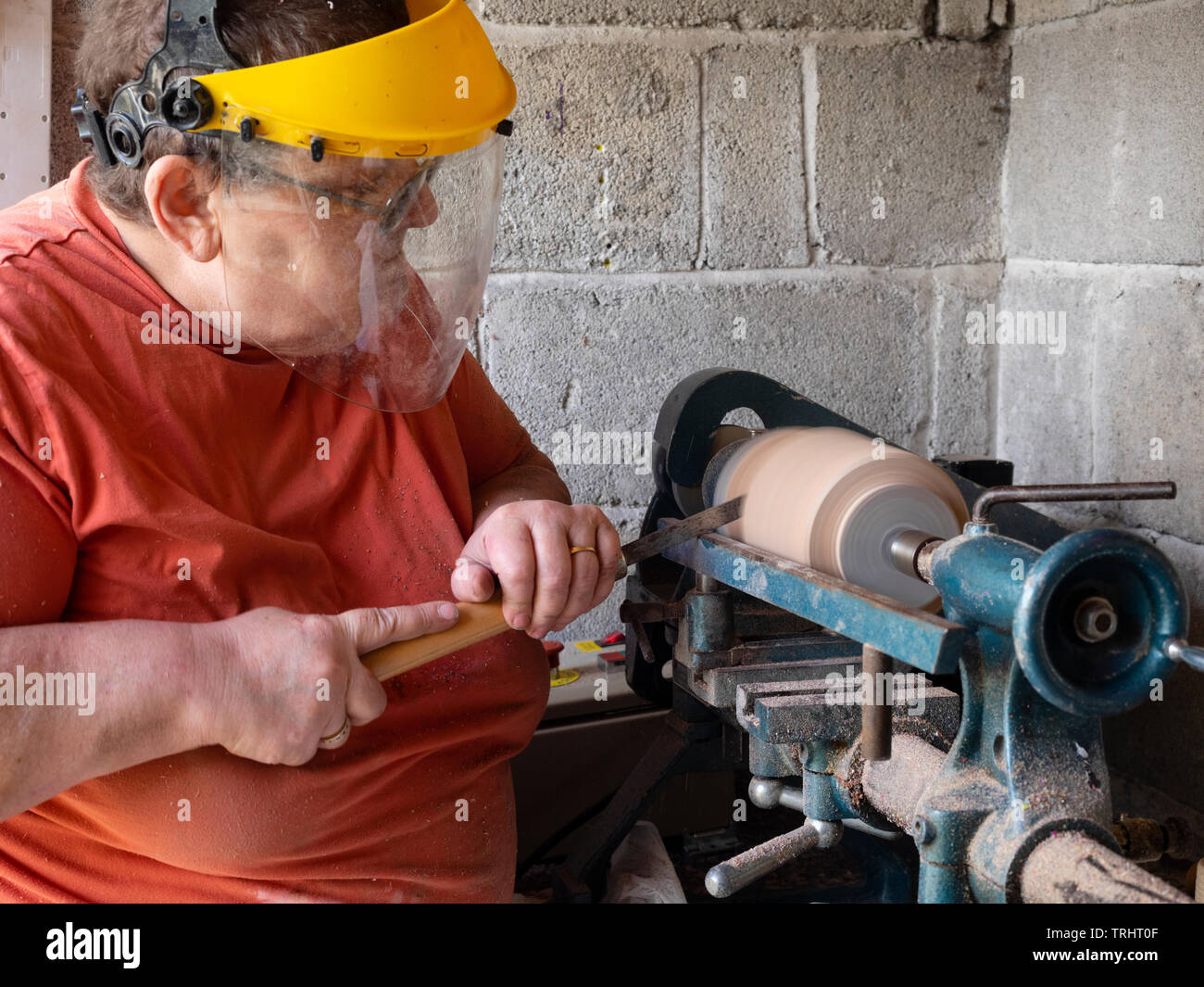 Mature, 65 year old, female crafter turning a wooden vase on her lathe Stock Photo