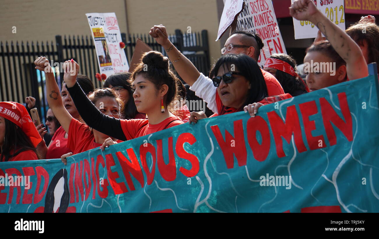 Indigenous or Native American women marching with a banner with fists in air. 2019 Women's March, Market Street, San Francisco, California, USA. Stock Photo