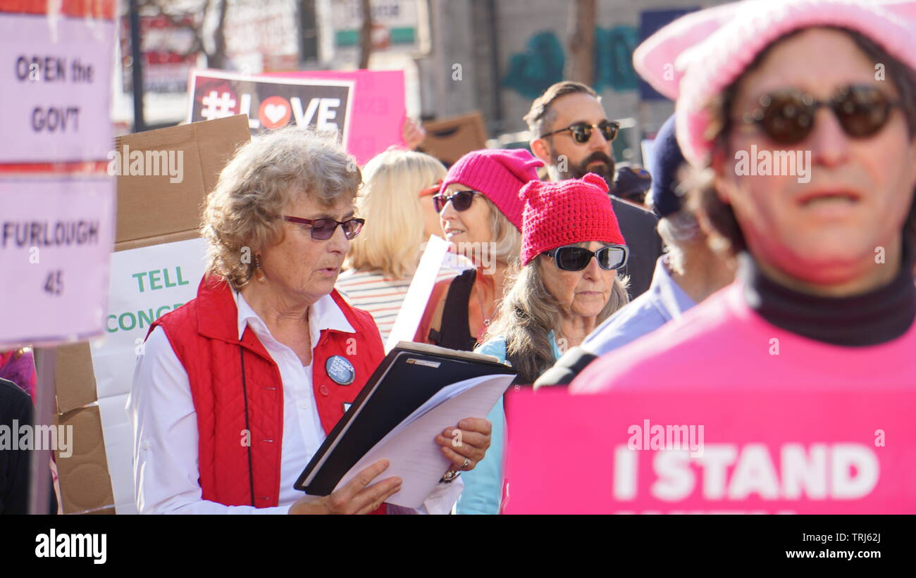 Woman singing at 2019 Women's March. Protesters in pink pussyhats. Anti-Trump protesters, Market Street, San Francisco, California, USA. Stock Photo