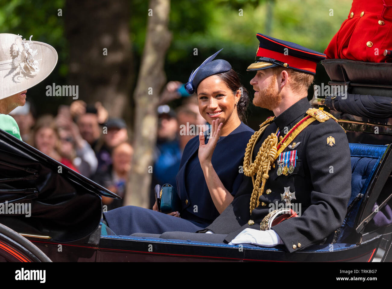 the-royal-family-and-massed-bands-and-troops-have-traveled-down-the-mall-to-horse-guards-parade-for-the-trooping-of-the-colour-2019-meghan-markle-duchess-of-sussex-waving-from-an-open-carriage-with-harry-in-uniform-eye-contact-TRKBG7.jpg