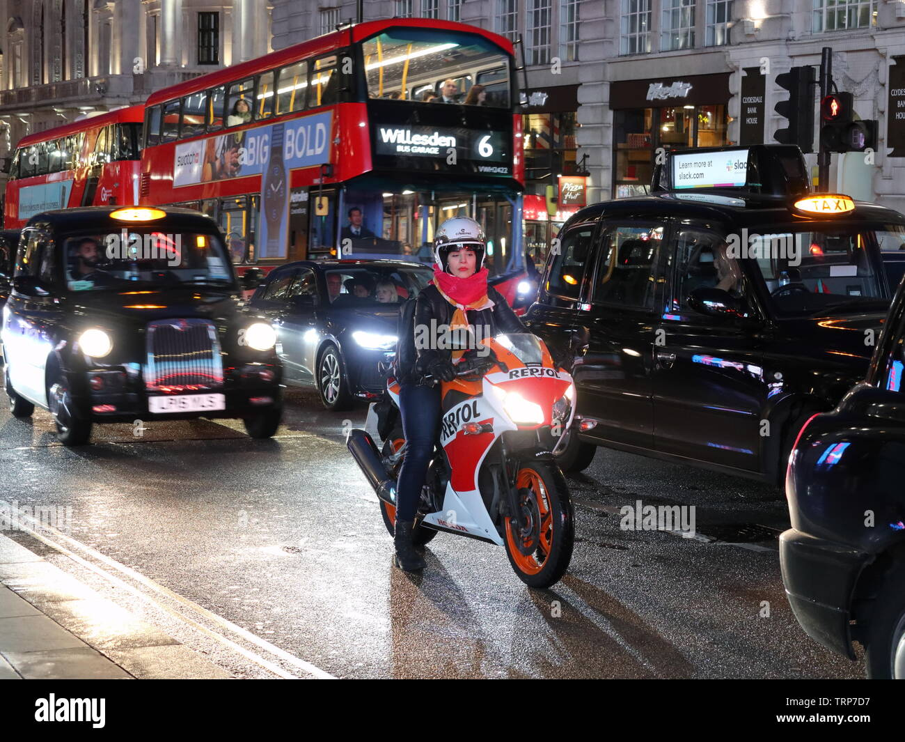 woman-biker-amonst-traffic-at-night-piccadilly-london-england-uk-TRP7D7.jpg