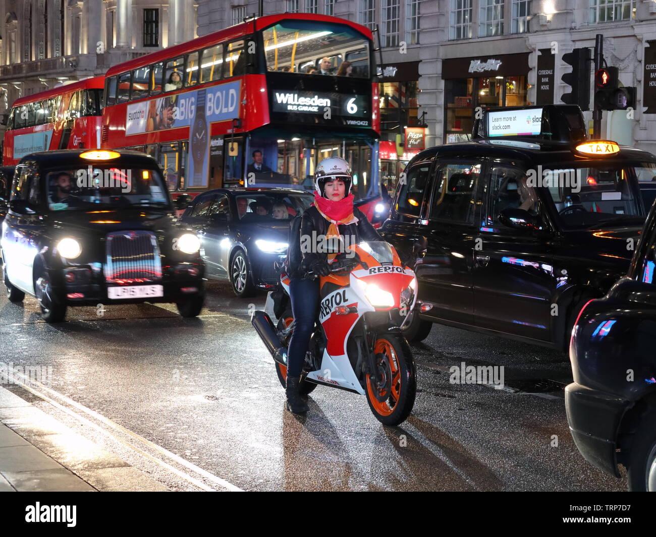 woman-biker-amonst-traffic-at-night-piccadilly-london-england-uk-TRP7D7.jpg