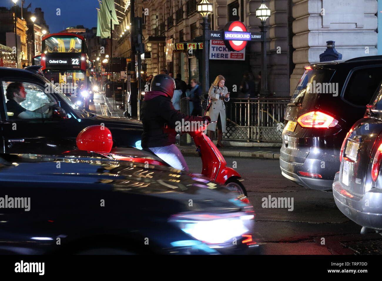 scooter-rider-weaves-through-taffic-at-night-piccadilly-london-england-uk-TRP7DD.jpg