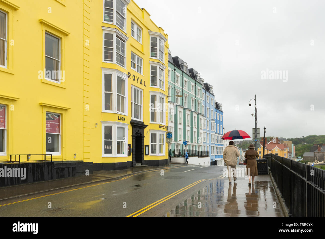 a-couple-walking-along-tenby-promenade-past-colourful-buildings-with-an-umbrella-on-a-rainy-day-pembrokeshire-wales-TRRCYX.jpg