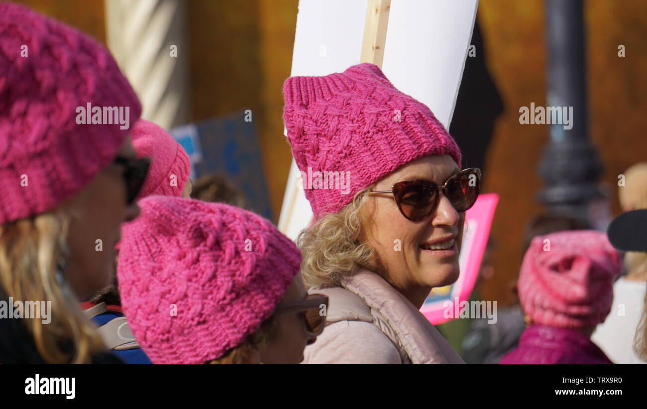 Woman wearing hand knit pink pussyhat in a sea of pink hats. 2019 Women's March, Anti-Trump Protest, Market Street, San Francisco, California, USA. Stock Photo