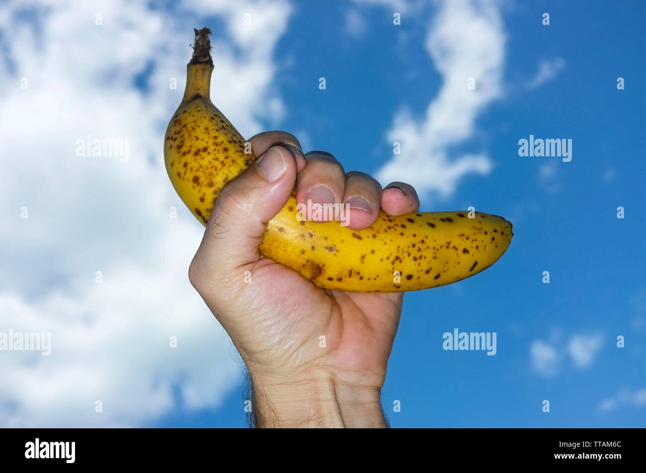 hand-of-a-man-holding-a-ripe-yellow-bana