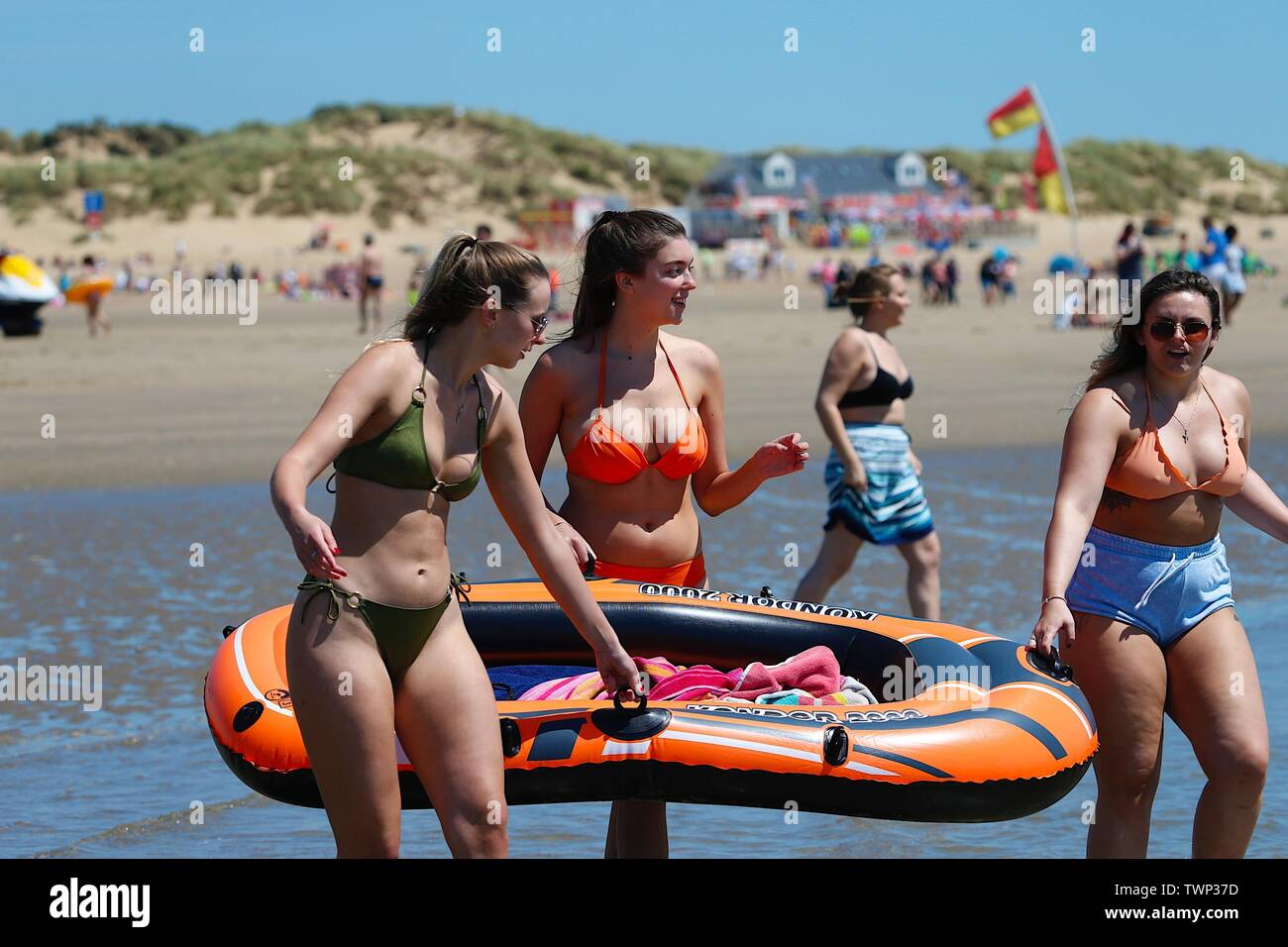 Camber, East Sussex, UK. 22nd June, 2019. A beautiful sunny start to the weekend in Camber, East Sussex as people arrive to the Camber Sands beach to enjoy the warm weather. A group of three young women carrying an inflatable dinghy boat along the beach. Credit: Paul Lawrenson 2019, Photo Credit: Paul Lawrenson/Alamy Live News Stock Photo