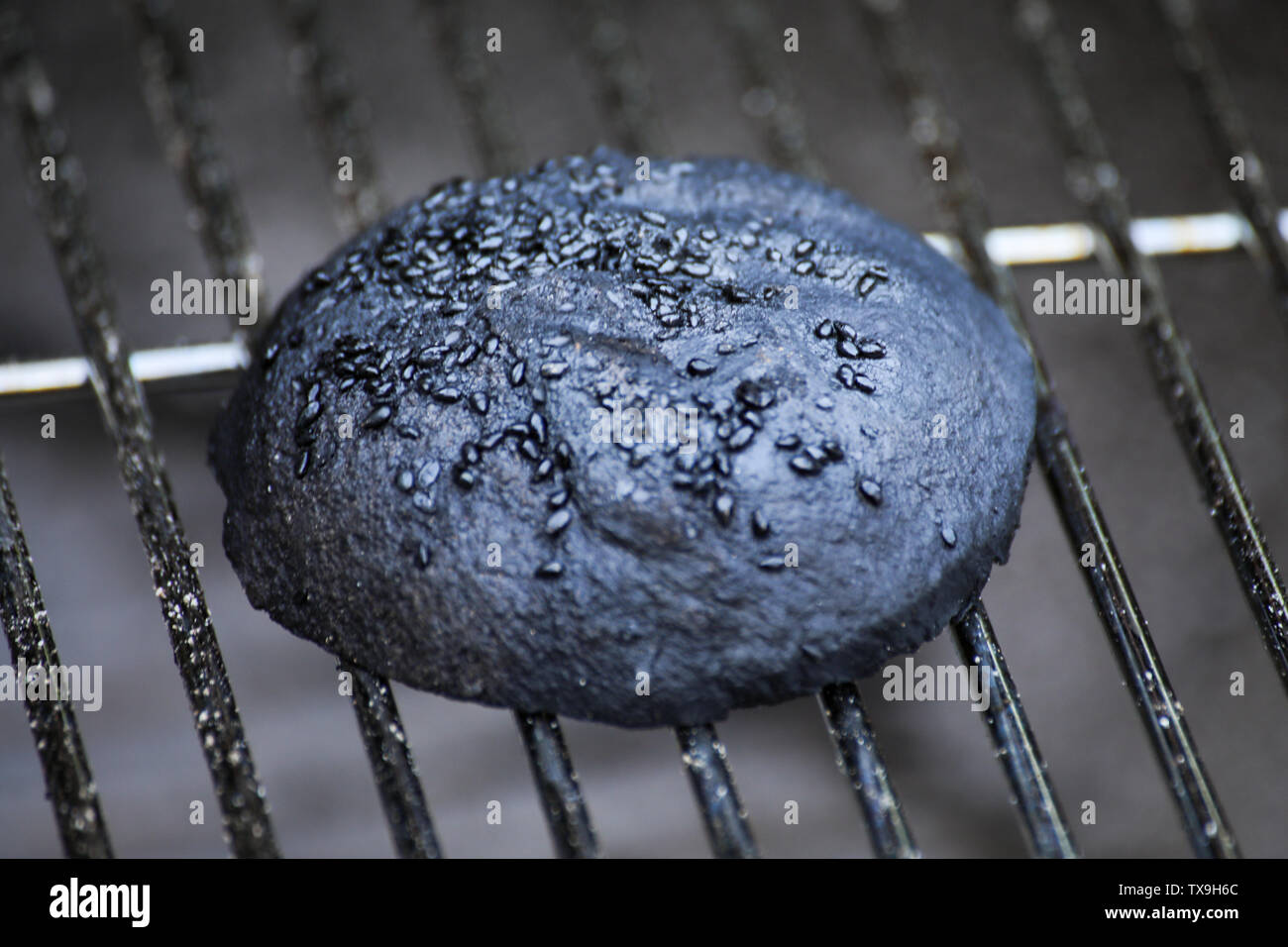 Burnt hamburger bun on grill grid Stock Photo