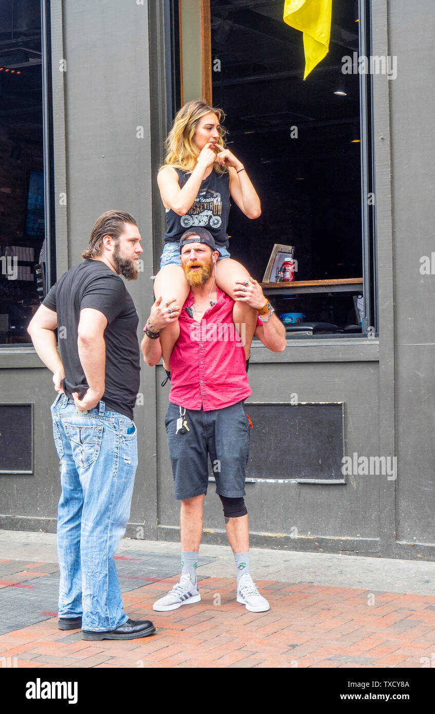 A woman sitting on a man's shoulders while he is talking to another man on Broadway at NFL Draft 2019 Nashville Tennessee USA. Stock Photo