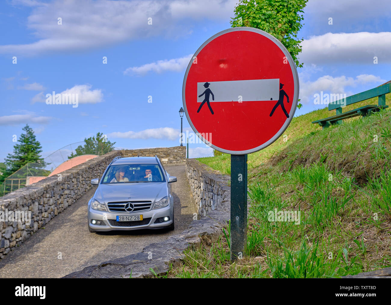 car-driving-through-no-entry-traffic-sign-modified-by-adding-human-shape-sticker-to-make-look-as-if-carrying-the-white-line-espelette-france-TXTT8D.jpg