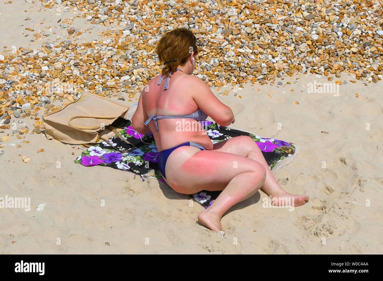 Lyme Regis, Dorset, UK.  27th June 2019. UK Weather.  A woman shows signs of sunburn as she lies on the beach at the seaside resort of Lyme Regis in Dorset enjoying a day of clear blue skies and scorching sunshine.   Picture Credit: Graham Hunt/Alamy Live News Stock Photo