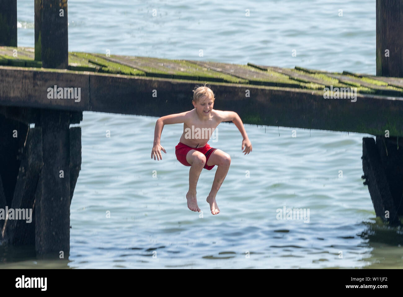 the-hot-heatwave-weather-has-brought-people-to-southend-to-enjoy-the-beaches-the-estuary-as-a-boy-jumps-into-the-river-thames-W11JF2.jpg