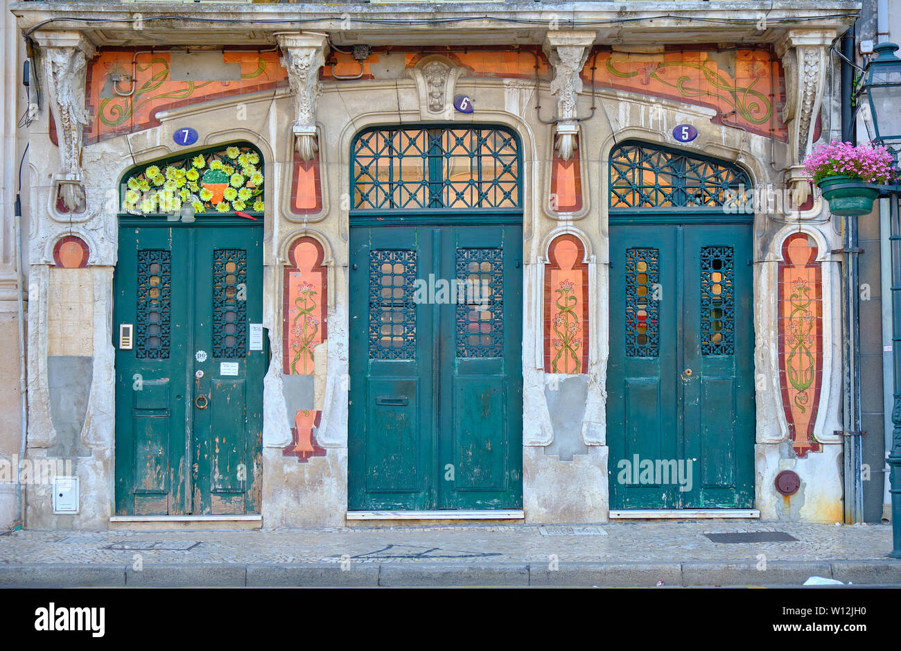 old-vintage-building-facade-in-art-nouveau-design-with-major-part-broken-and-crumbling-aveiro-portugal-W12JH0.jpg