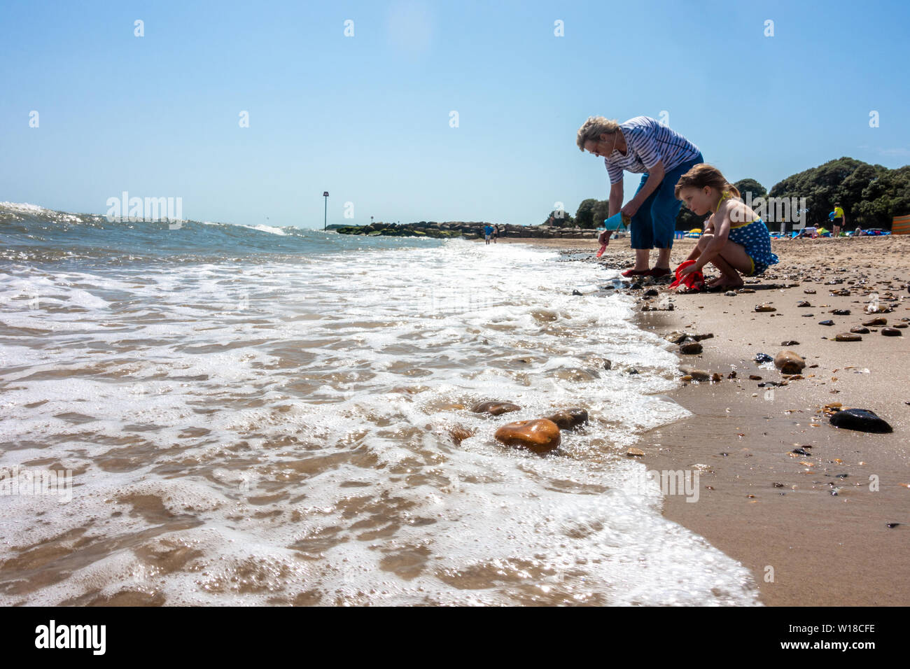 a-young-child-plays-with-her-mum-at-the-waters-edge-on-avon-beach-at-mudeford-christchurch-in-dorset-uk-on-a-hot-summer-day-with-blue-sky-W18CFE.jpg