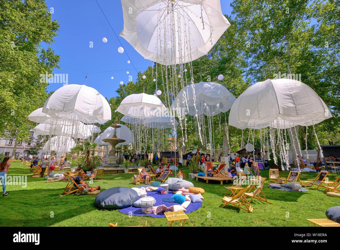 zagreb-croatia-july-1-2019-lumen-station-installation-in-park-outdoor-reading-pods-in-green-city-park-under-squid-like-hanging-umbrellas-W18ERA.jpg