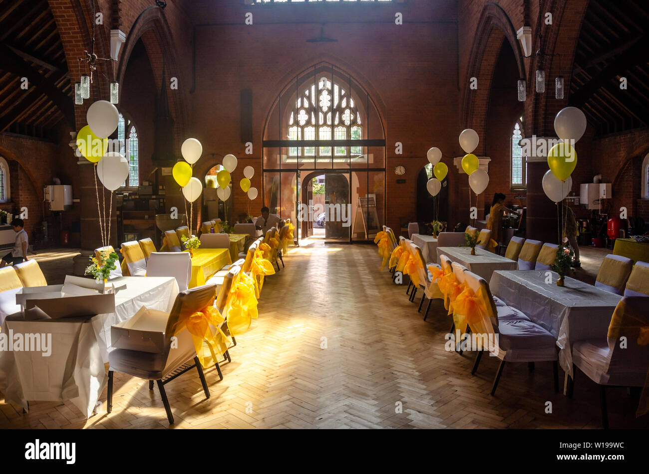 a-church-hall-laid-out-with-tables-and-chairs-dressed-in-white-fabric-with-yellow-ribbon-bows-ready-for-a-party-or-reception-W199WC.jpg