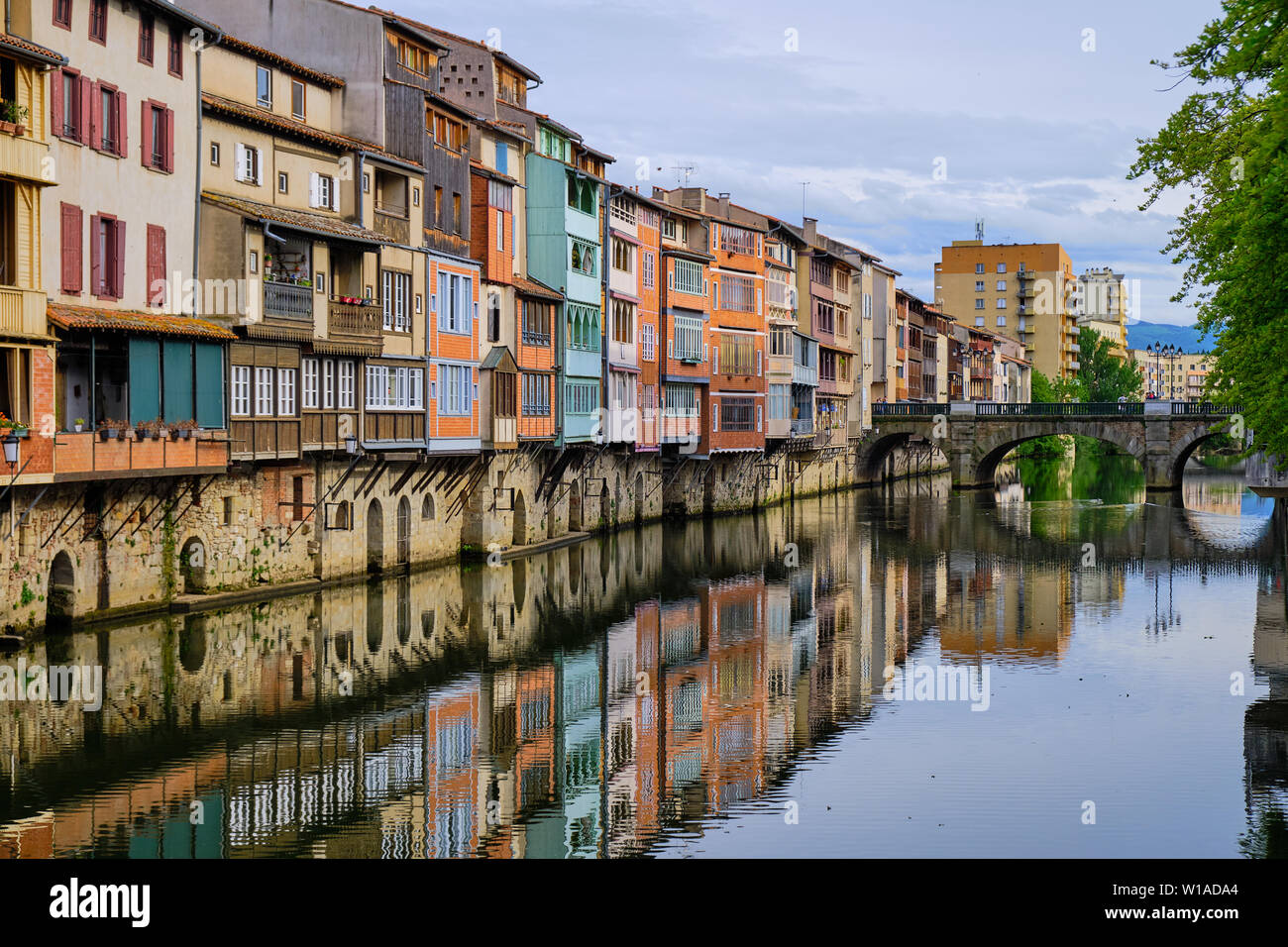 View of the Castres architecture on houses along the Agout river.  Angled view from side of river with house reflection  leading to old bridge. Stock Photo