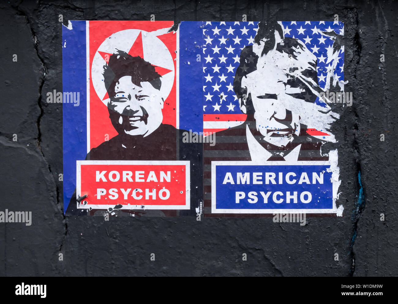 "Political poster on black surface depicting leaders of North Korea and United States of America under title ""Psycho"".  Attempt made to remove. Stock Photo"