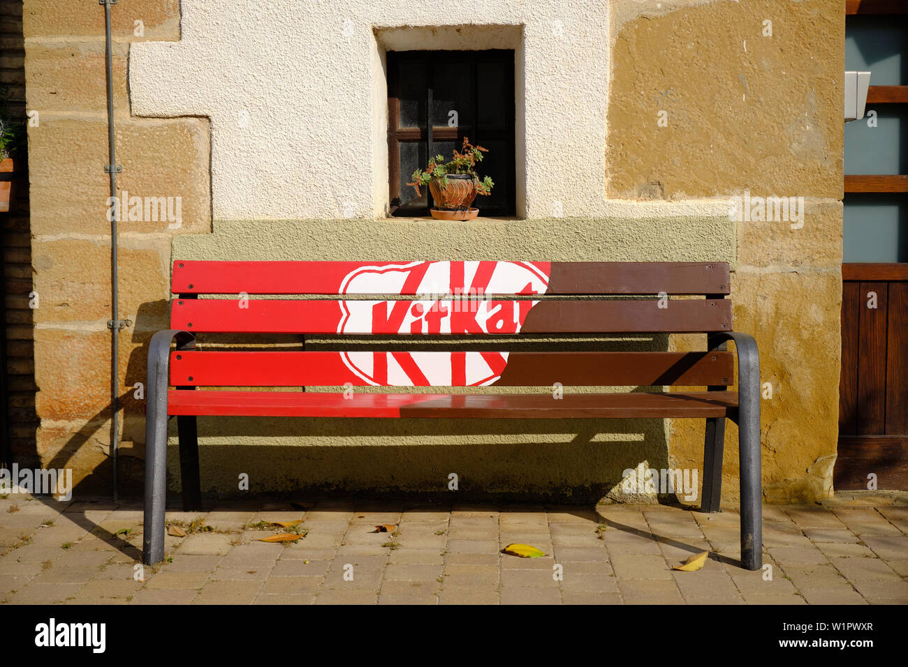 Bench with KitKat advertising on sunny day.  Arre, Spain. Stock Photo
