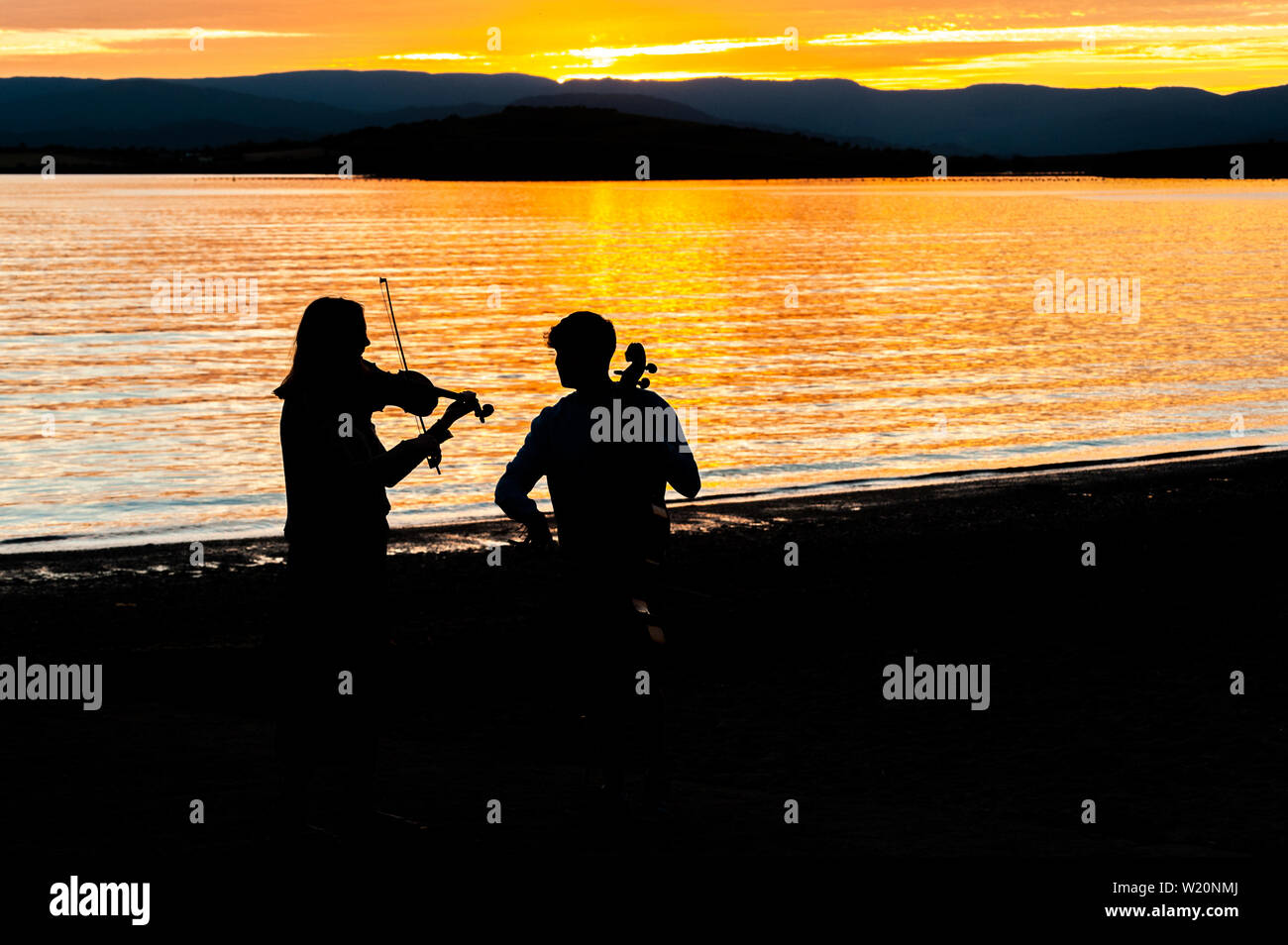bantry-west-cork-ireland-4th-july-2019-bantry-is-hosting-the-west-cork-chamber-music-festival-this-week-which-brings-classical-musicians-from-far-and-wide-to-play-at-the-various-concerts-in-the-town-violin-player-kate-fleming-and-cellist-callum-owens-both-from-cork-played-as-the-sun-went-down-this-evening-credit-andy-gibsonalamy-live-news-W20NMJ.jpg