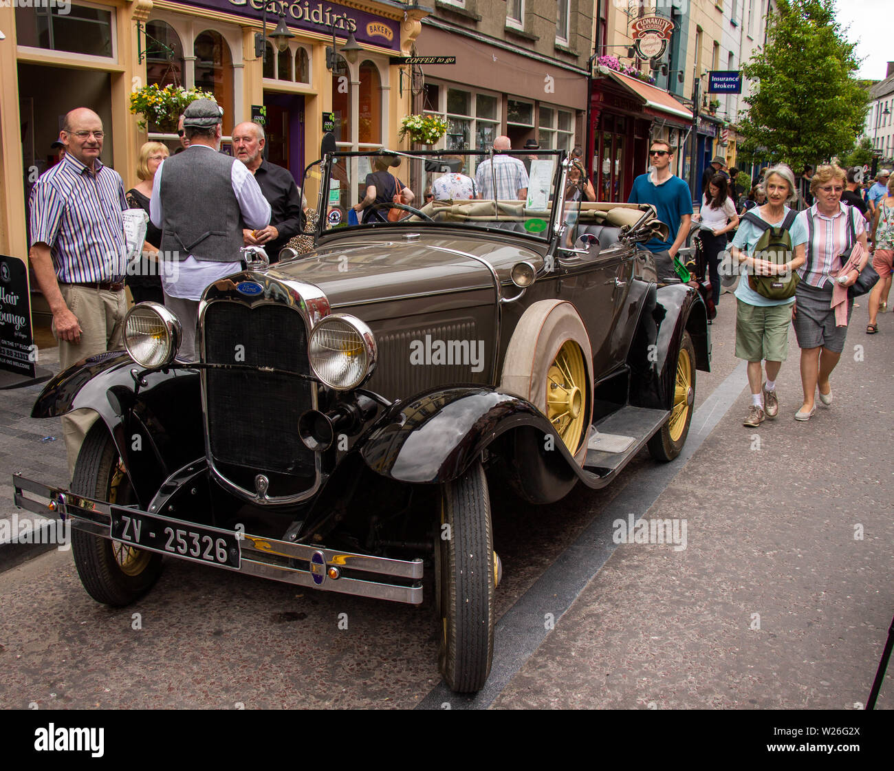 vintage-ford-soft-top-motor-car-parked-on-a-high-street-W26G2X.jpg