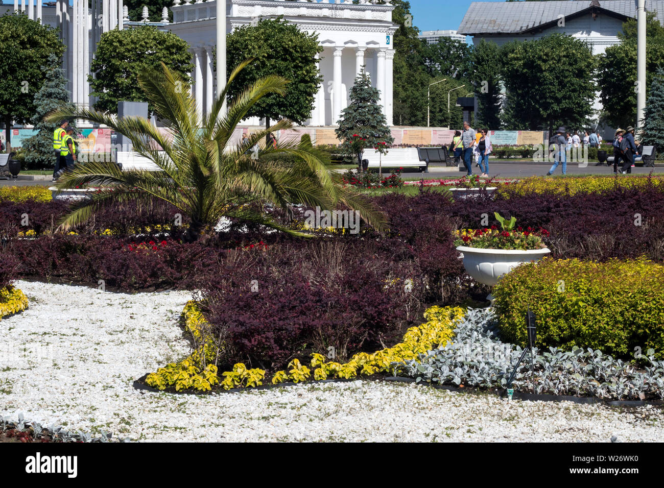 Moscow, RUSSIA - July 2, 2019 , A flower bed with a palm tree and white stones in front of the pavilion of Uzbekistan at VDNKh Stock Photo
