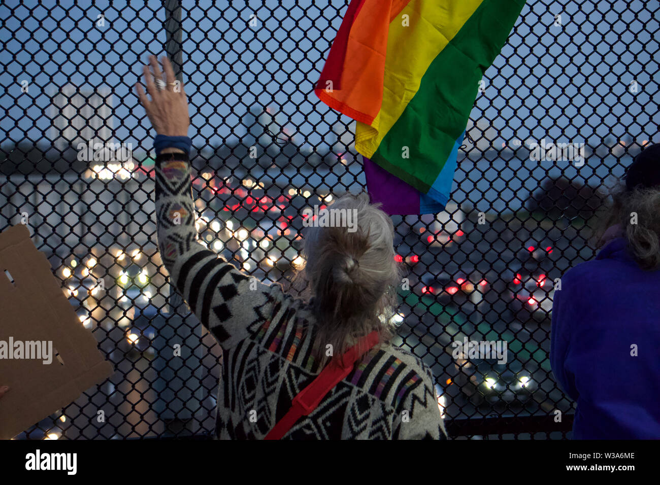 Protestor on the Berkeley Pedestrian Bridge over Highway 80, looking south, as part of the Lights For Liberty vigil to protest US detention camps. Stock Photo