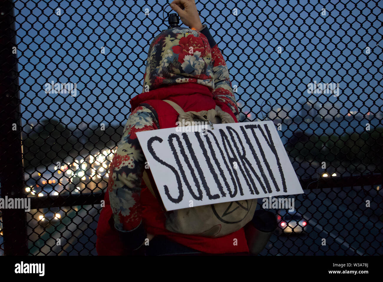 protestor-with-solidarity-sign-over-highway-lights-for-liberty-vigil-to-protest-us-detention-centers-and-ice-camps-for-immigrant-children-berkeley-W3A78J.jpg