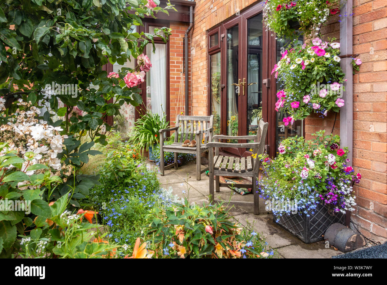 a-pair-of-wooden-chairs-in-a-corner-of-a-garden-W3K7WY.jpg