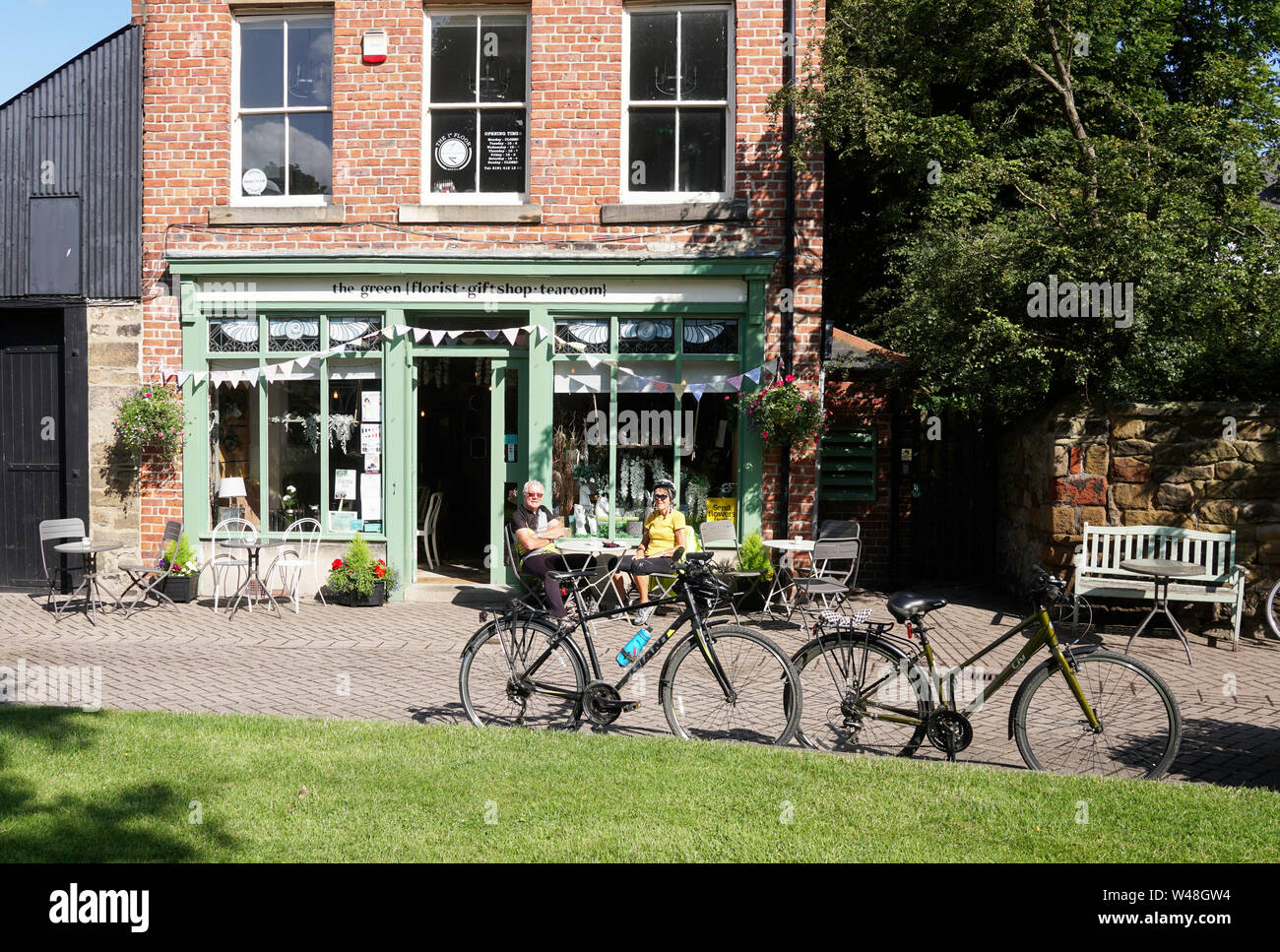 an-older-couple-of-cyclists-sit-outside-