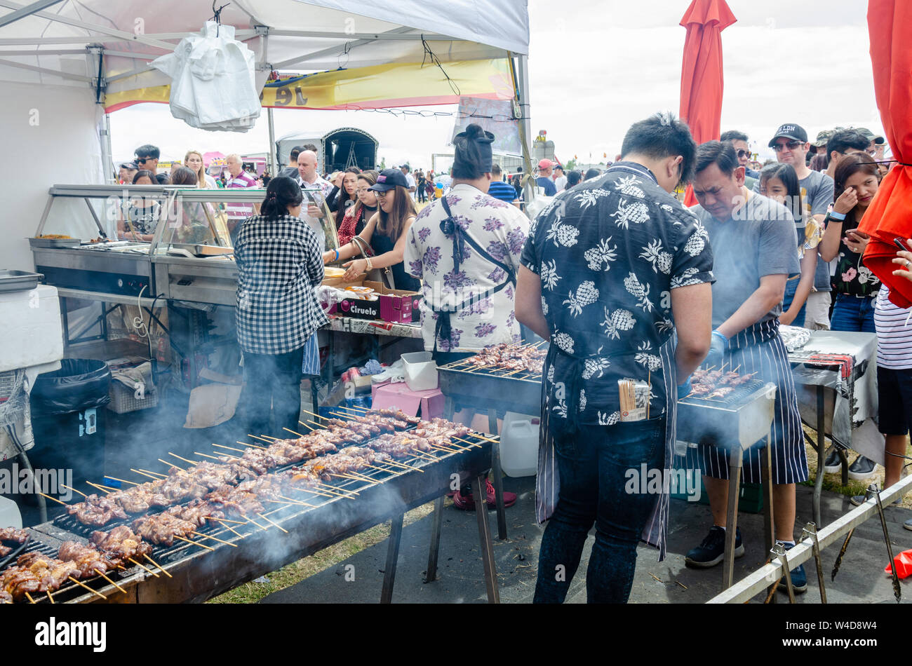 a-street-food-catering-stall-at-a-filipino-event-in-london-pork-barbeque-cooks-on-grills-attended-by-two-men-W4D8W4.jpg