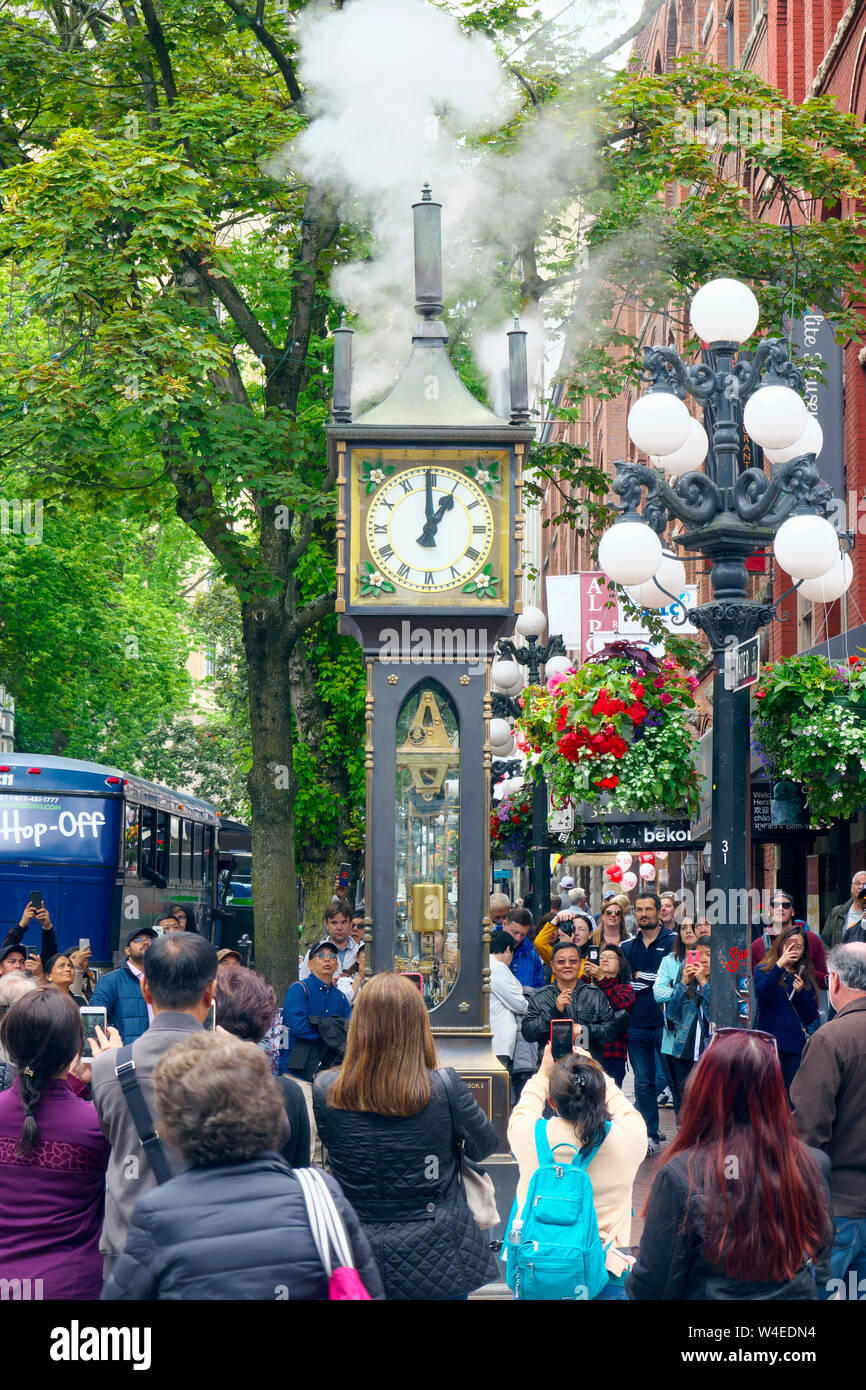 Street scene showing crowds watching the Gastown Steam Clock as it puffs steam at the top of the hour. Stock Photo
