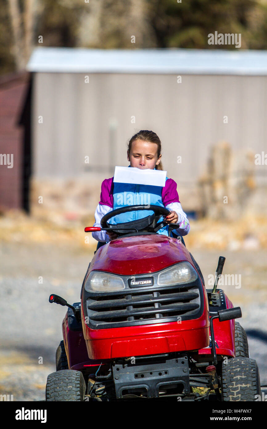 Young blond girl on a lawn tractor delivering the mail Stock Photo