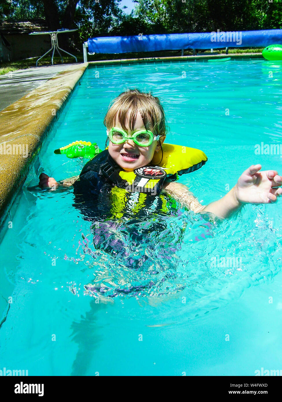 A fully equipped young girl safely swims alone in a pool Stock Photo