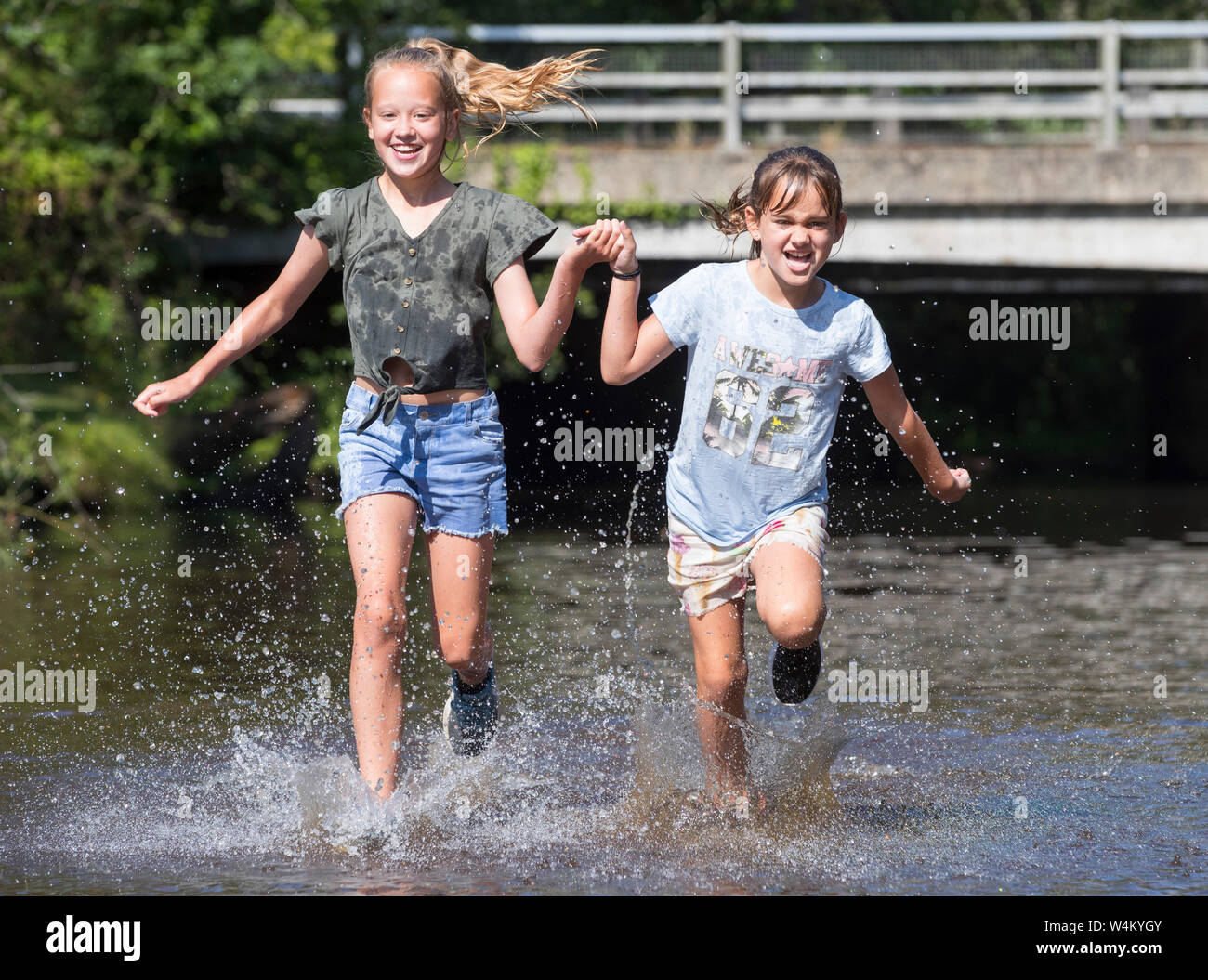 New Forest Hampshire, 24th July 2019. UK Weather: Sisters Ebony 11 and Isobella 8 cool off in the river at Brockenhurst in the New Forest as the hot weather continues across the UK. Credit Stuart Martin/Alamy Live News Stock Photo