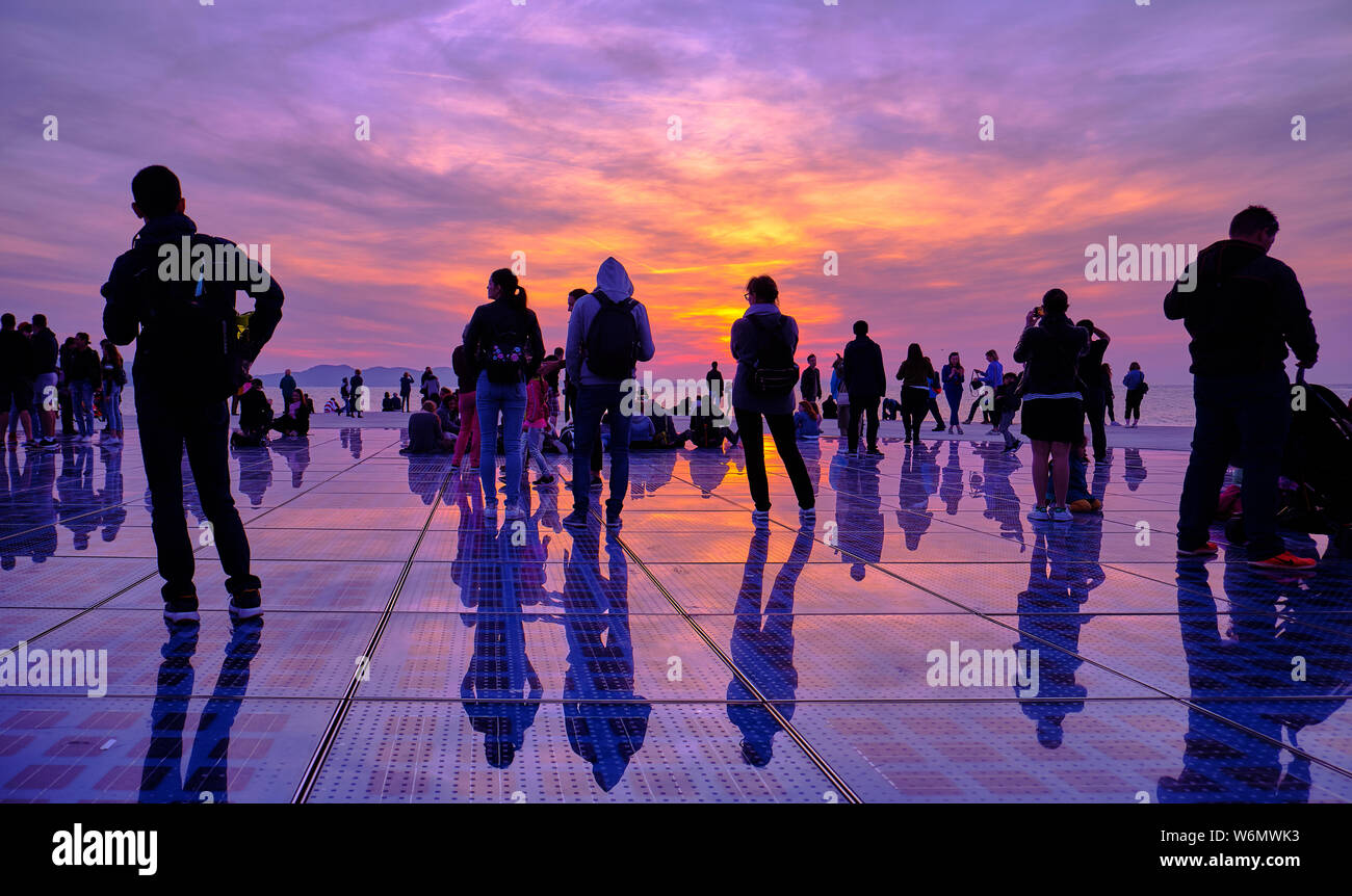 silhouette-of-people-against-an-orange-and-purple-sunset-of-the-greetings-to-the-sun-monument-zadar-croatia-april-2019-W6MWK3.jpg