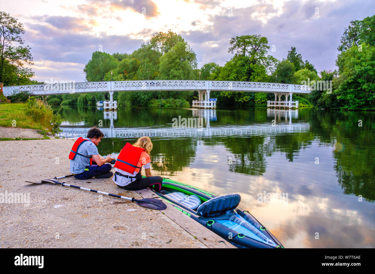 a-couple-of-canoeists-sit-on-the-bank-of-the-river-thames-in-front-of-the-whitchurch-bridge-which-links-the-villages-of-whithcurch-and-pangbourne-W7T6AE.jpg