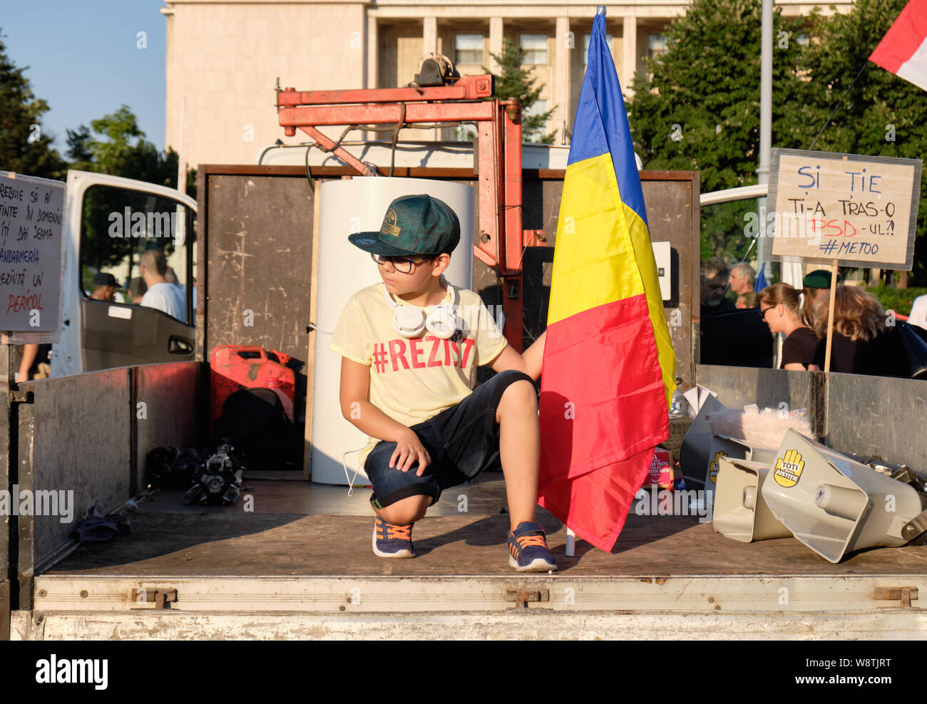 Young boy with REZIST t-shirt and romanian flag at protest against allegations of on-going corruption within the government of Romania, in Bucharest Stock Photo