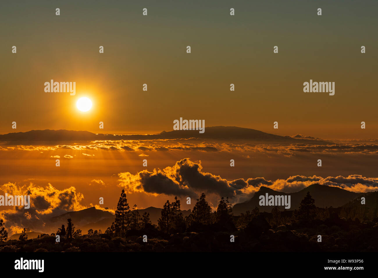 bright-hot-sun-shining-over-la-palma-on-to-clouds-and-volcanic-landscape-of-the-island-of-tenerife-late-in-the-evening-giving-a-deep-orange-glow-to-th-W93P56.jpg