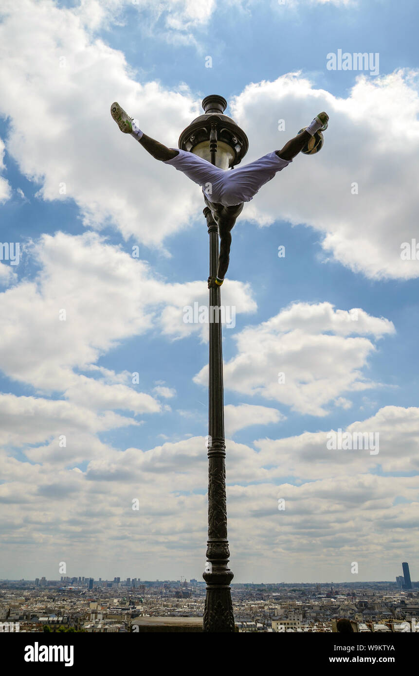 street-performer-in-paris-france-performing-on-a-lamp-post-at-sacr-cur-overlooking-the-city-football-skills-and-acrobatic-athleticism-skyline-W9KTYA.jpg