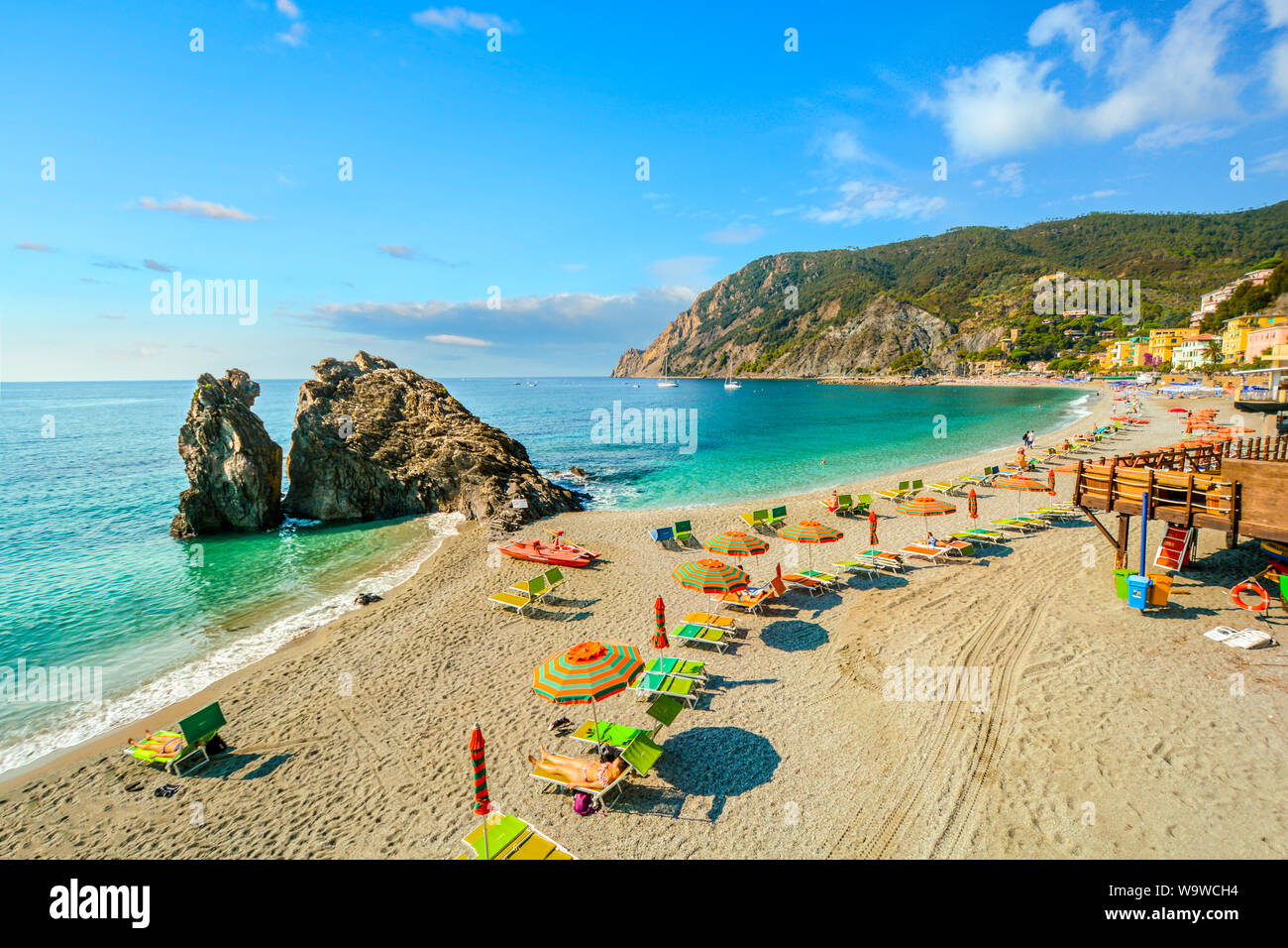 Chairs and umbrellas fill the Spiaggia di Fegina, the wide sandy beach in front of the old section of the village of Monterosso al Mare, Italy Stock Photo