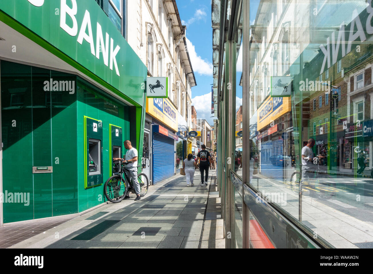 a-man-uses-an-atm-machine-at-the-slough-high-street-branch-of-lloyds-bank-the-scene-is-seen-reflected-in-a-glass-bus-stop-WAAW2N.jpg
