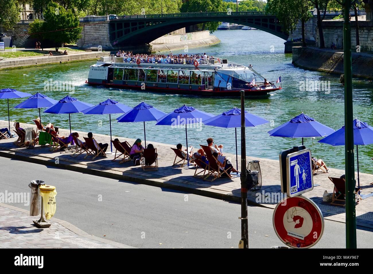 people-relaxing-under-blue-umbrellas-in-