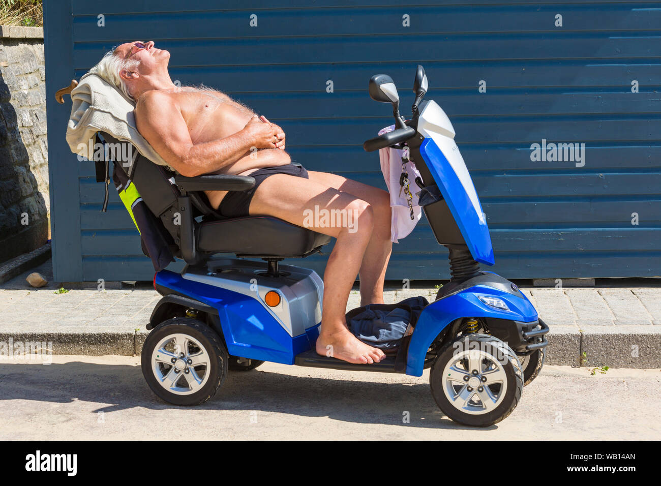 Bournemouth, Dorset UK. 23rd Aug 2019. UK weather: an overcast start turns into a lovely warm sunny day as beachgoers head to the seaside at Bournemouth beaches to enjoy the sunshine, as temperatures are set to get higher for the Bank Holiday weekend. Paul soaks up the sun sunbathing on his scooter. Credit: Carolyn Jenkins/Alamy Live News Stock Photo