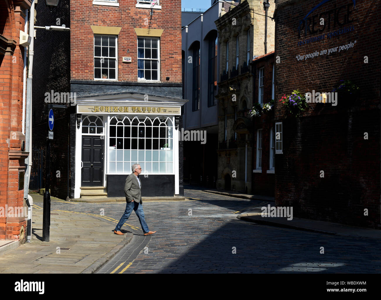 Man crossing cobbled street called The Land of Green Ginger, in the old town, Hull, East Yorkshire, England UK Stock Photo