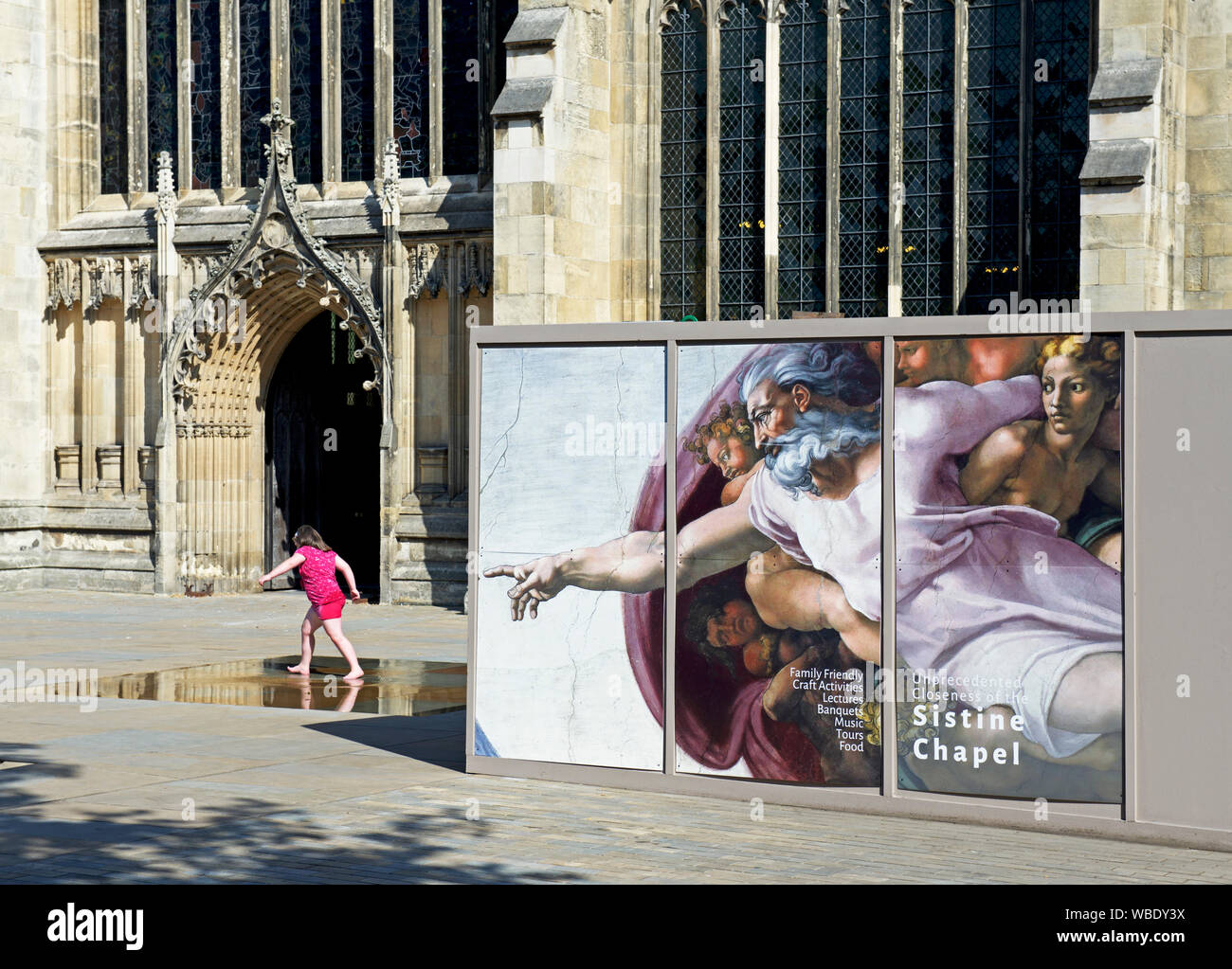 girl-playing-next-to-poster-announcing-an-art-exhibition-of-michaelangelos-work-outside-the-minster-hull-east-yorkshire-england-uk-WBDY3X.jpg