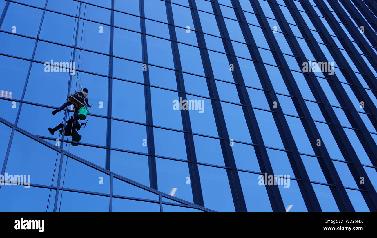 Exterior window washers dangling outside Marquette Plaza, the former Federal Reserve Bank building at 250 Marquette, Minneapolis, Minnesota. Stock Photo