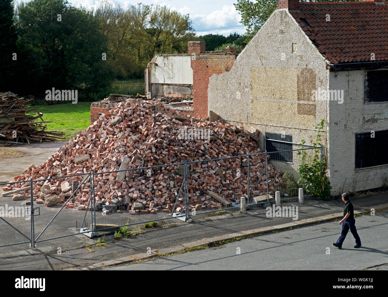 man-walking-past-demolished-building-now-just-a-pile-of-bricks-in-thorne-south-yorkshire-england-uk-WGK1JJ.jpg