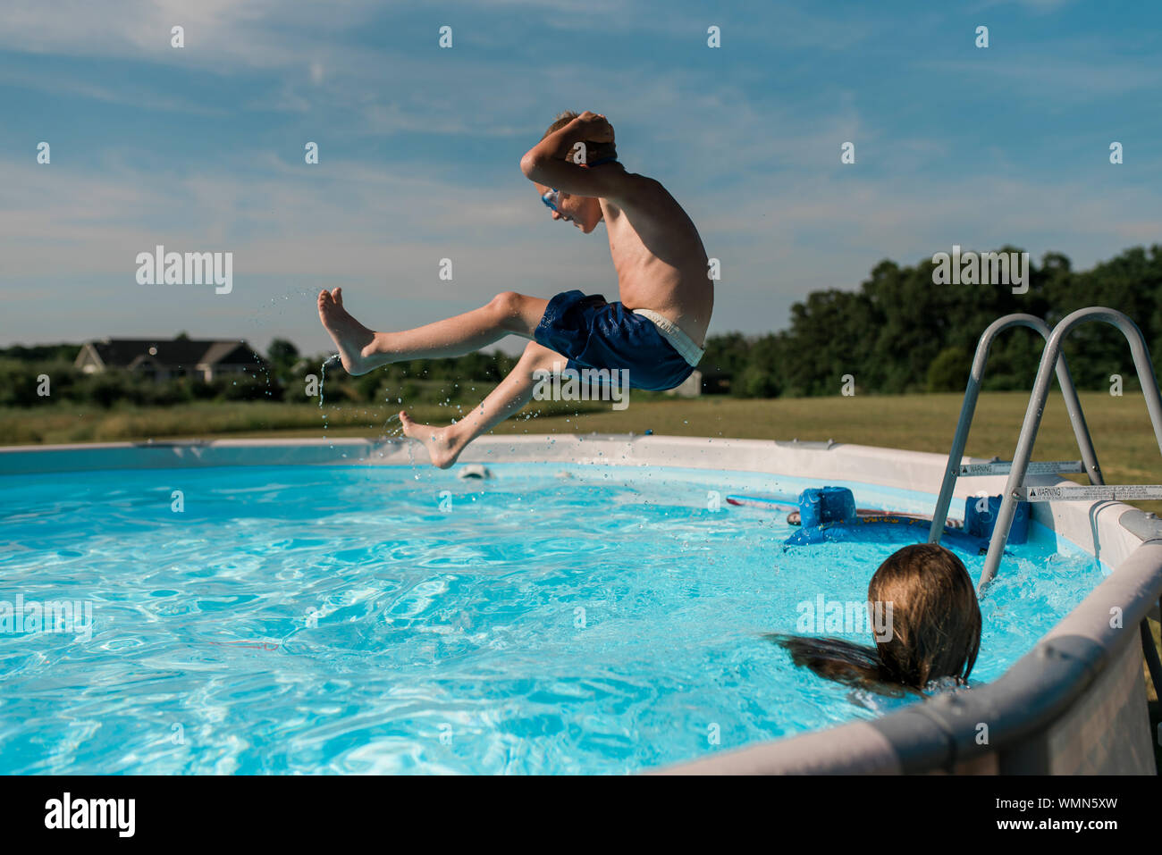 Young boy jumps into pool on a sunny summer day in the backyard Stock Photo